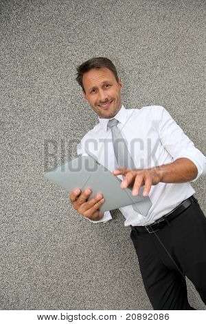 Smiling salesman using electronic tablet poster