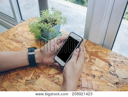 Close up businessman using cell phone in coffee shop.