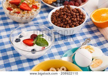 Rich continental breakfast menu. Muesli, orange half , yogurt and boiled eggs for tasty morning meals on checkered tablecloth