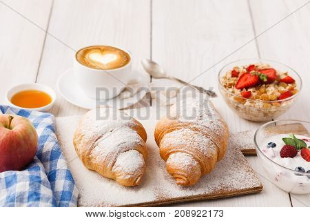 Traditional french breakfast menu . Yogurt with fresh berries, cup of coffee croissants on wooden table, copy space