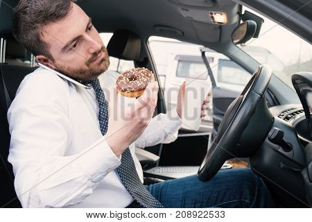 Man Having Breakfast And Driving Seated In Car