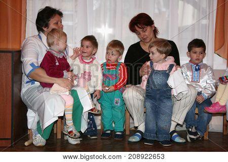 LUTSK UKRAINE - 19 December 2008: Caregiver and little orphan children in an orphanage