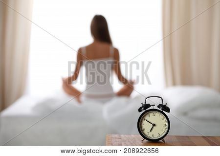 Alarm clock standing on bedside table has already rung early morning to wake up. Woman do yoga in bed in background. Early awakening, healthy lifestyle contemplation concept