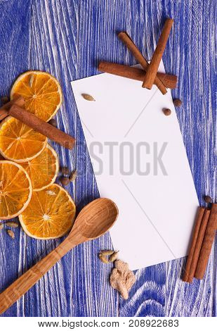 Christmas decoration. Blank with dried orange slices, cinnamon and spices on a wooden blue background. Top view.