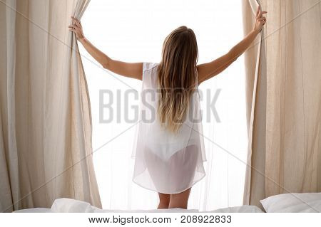 Happy woman opening window curtains at home, back view. Good morning, new day, weekend, holidays concept.