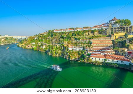 Aerial view of tourist boat in Douro River and Unesco Monastery of Serra do Pilar from Dom Luis I Bridge in Vila Nova de Gaia, Porto, Portugal. Oporto urban scenic landscape in the blue sky.