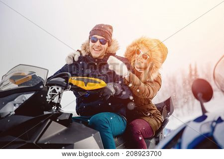 Lovers. guy and girl on a snowmobile. Concept winter vacation. Shine of the sun.