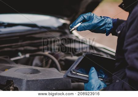 man checks the spark plugs in the car workshop