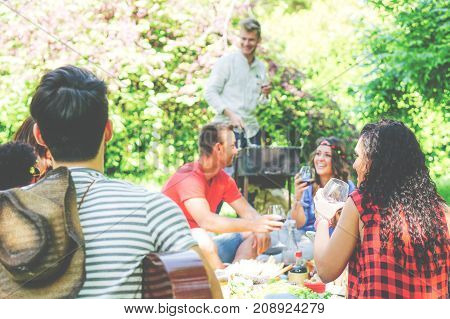 Group of friends having a picnic in a park while drinking red wine - Young people hanging out having fun and grilling meat - Traditional meal friendship outdoor - Focus on the girl on the right side