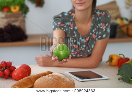 Close-up of female hand holding green apple in kitchen interiors. Many vegetables and other meal at glass table are ready for been cooked soon.