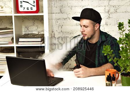 Young Man Sitting In Office With A Cup Of Coffee And Vaping
