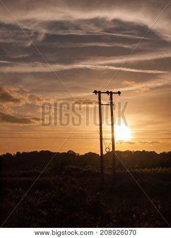 Stunning Sun Set Over Field And Metal Wooden Poles Electricity Train Track