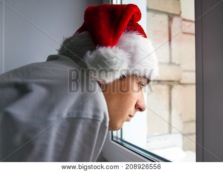 Pensive Young Man in Santa's Hat by the Window