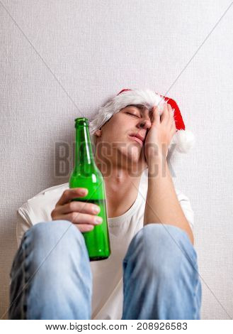 Sad Young Man in Santa's Hat with a Beer by the Wall
