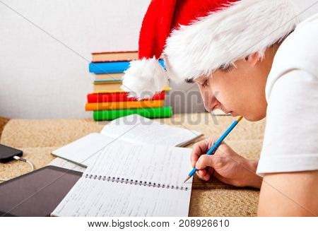 Student in Santa's Hat doing Homework on the Couch