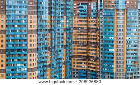 Windows and balconies of a multi-storey residential building as a background.