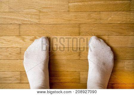 Male feet in woolen socks stand on wooden floor