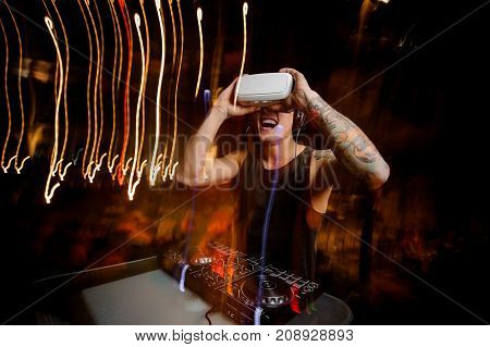 Young DJ in virtual reality glasses dressed in black shirt and with tattoo plays the track in club
