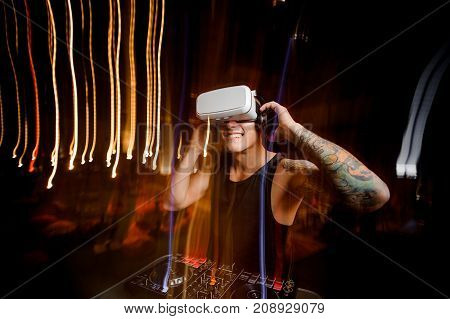 Smiling DJ in virtual reality glasses dressed in black shirt and with tattoo plays the track in club
