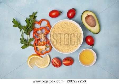 couscous and fresh vegetables: tomatoes peppers lemon avocado parsley olive oil on a blue background. view from above