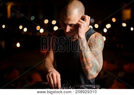 Handsome young bald DJ with tattoo and in headphones mixes music in the night club