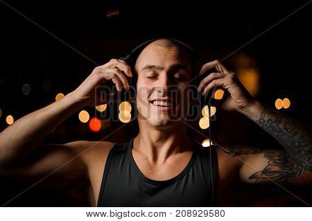 Smiling young tattooed DJ in headphones on the background of night club lights with closed eyes