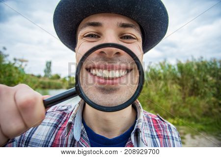 A cheerful young man with a funny face in a hat holds a magnifying glass. Let's celebrate!