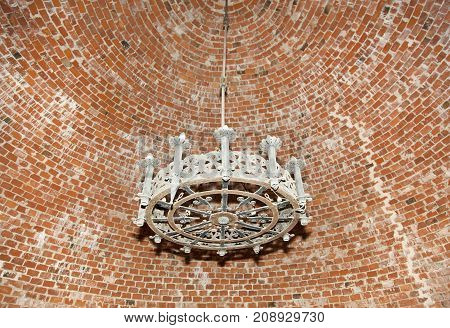 The dome shape brick ceiling with a brass chandelier in 14th century Turaida Castle tower (Latvia).