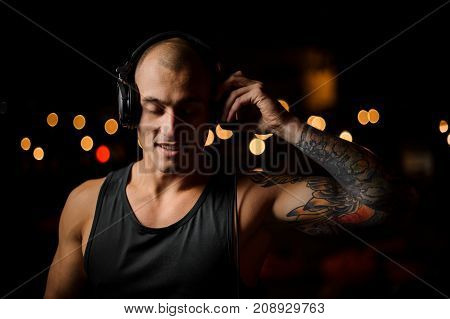 Tattooed DJ in headphones feels the music on the background of night club lights with closed eyes