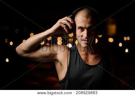 Handsome nightclub DJ in headphones feels the music on the background of night club lights