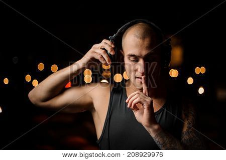 Tattooed nightclub DJ in headphones feels the music on the background of night club lights