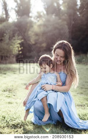 Charming mom with small daughter in blue long sitting on the grass