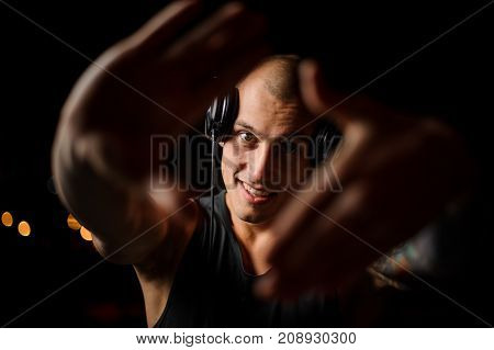 Young smiling nightclub DJ in headphones looks at the camera through the palms on the dark background
