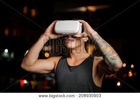 Fascinated muscular and tattooed young man dressed in black shirt in night vision glasses on the background of lights