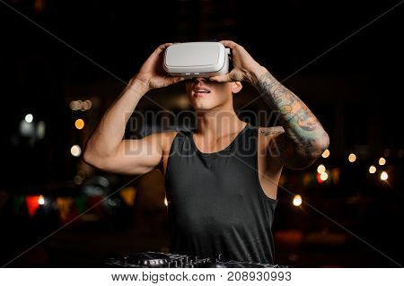 Fascinated muscular and tattooed man dressed in black shirt in night vision glasses on the background of lights