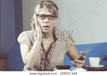 Young woman getting bad news by phone
