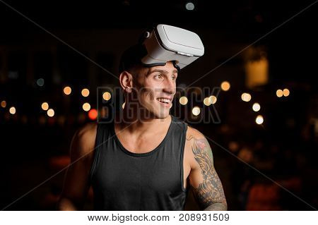 Handsome muscular and tattooed man dressed in black shirt in night vision glasses looks away on the background of lights