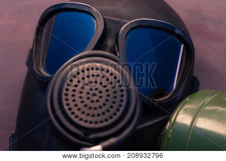 Black gas mask with blue reflection in the glass on a beautiful background.