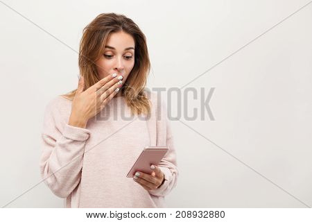 Young casual girl looking shocked while posing with smartphone in studio.