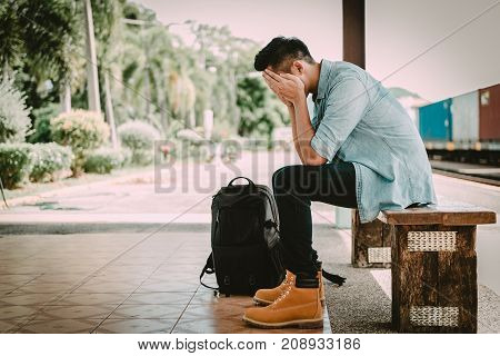Depressed Asian traveler man waiting at train station after miss a train or delay