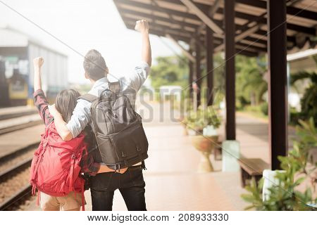 Back view of Asian traveler couple celebrate with hand up for start their journey at train station