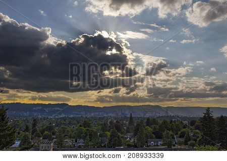 Afternoon sun rays through clouds over city of Portland Oregon downtown skyline
