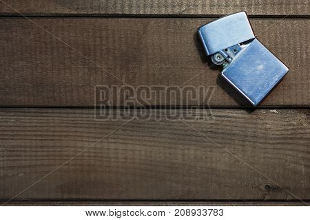 Gasoline lighter and cigarette, metal lighter on a wooden background
