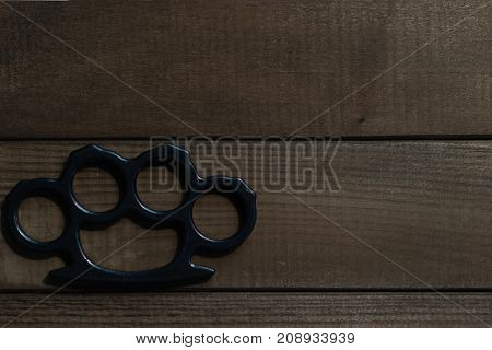 Brass knuckles on a beautiful brown wooden background.