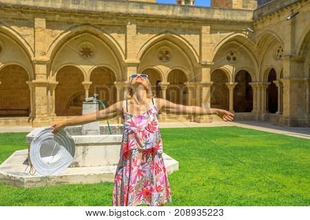 Freedom woman with open arms at old Coimbra Cathedral cloister. Se Velha de Coimbra is one of most important romanesque buildings in Portugal. Female tourist enjoying in university town of Coimbra.