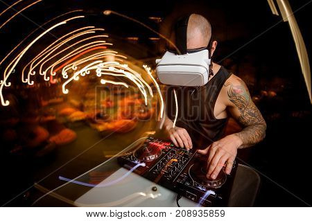 Male DJ in glasses of virtual reality in the process of work. Fashion Party