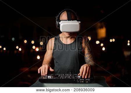 Man plays a DJ mixer with virtual reality glasses. The concept of the future