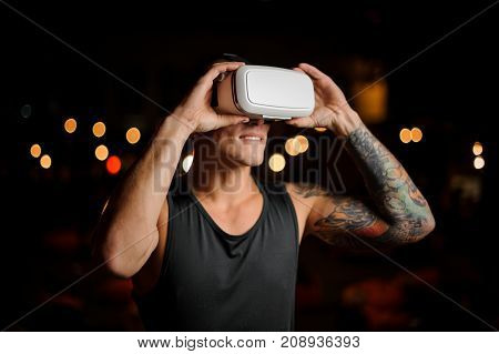 Young sexy guy bites his lip in virtual reality glasses against the backdrop of the night city.