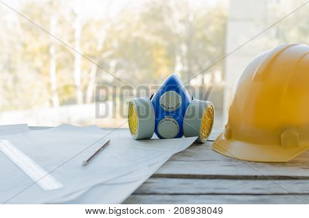 Engineering workplace drawings protective construction helmet and dust mask on the desktop