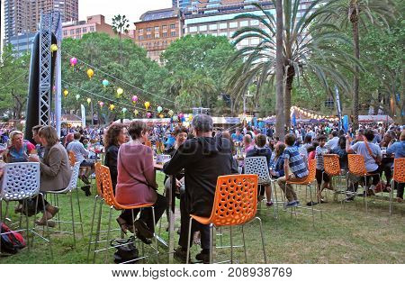 Sydney Australia - October 11 2015: People at the tables are enjoying dining and festivities during Night Noodle Market. A Sydney food institution since 2013 the Sydney Night Noodle Markets at Hyde Park is a part of Good Food Month.